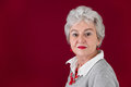 Portrait of serious elderly woman in red and gray Royalty Free Stock Images