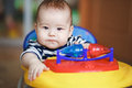 Portrait serious stern baby behind the wheel of a toy car. Royalty Free Stock Photo