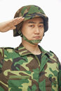 Portrait of serious young man in military uniform saluting studio shot Royalty Free Stock Photo
