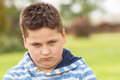Portrait of a seven years old young caucasian boy an angry in the shirt with the blue and white stripes in the park Royalty Free Stock Photos
