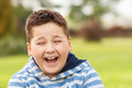 Portrait of a seven years old young caucasian boy laughing in the shirt with the blue and white stripes in the park Royalty Free Stock Photo