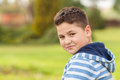 Portrait of a seven years old young caucasian boy in the shirt with the blue and white stripes in the park Royalty Free Stock Image