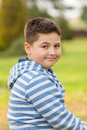 Portrait of a seven years old young caucasian boy in the shirt with the blue and white stripes in the park Stock Photography