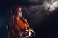 Portrait of sexy astronaut girl in orange latex ca catsuit holding vintage underwater camera case Royalty Free Stock Photo