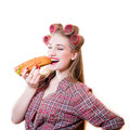 Portrait of sexy beautiful blond young woman in curlers with eyes closed having fun eating hot dog on white copy space background Royalty Free Stock Photo