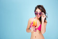 Portrait of a sexy beautiful girl holding cocktail in sunglasses young brunette isolated on the blue background Stock Photo
