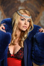 Portrait of sexy glamour woman with long blond hair wearing luxurious blue fur coat and seductive red lingerie. Royalty Free Stock Photo