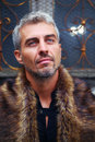 Portrait of a sexy man in wolf  fur and ornamental medieval window on background Royalty Free Stock Photo