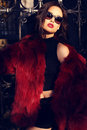 Portrait of sexy woman with dark hair in luxurious fur coat and sunglasses fashion outdoor photo beautiful wearing red Stock Photography