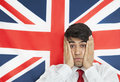 Portrait of a shocked indian man with hands on cheeks against british flag Royalty Free Stock Photos
