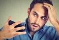 Portrait, shocked man feeling head, surprised he is losing hair