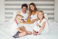 Portrait of siblings with parents on bed Royalty Free Stock Photo