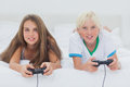 Portrait of siblings playing video games while they are lying on bed Stock Photography