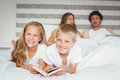 Portrait of siblings relaxing with parents on bed Royalty Free Stock Photo