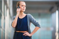 Portrait of a sleek young woman calling on a smartphone in an urban city context shallow dof color toned image Stock Photography