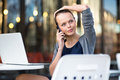 Portrait of a sleek young woman calling on a smartphone and using her laptop in an urban city context shallow dof color toned Stock Photography