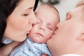 Portrait of a sleeping baby and parents kiss on the cheek Royalty Free Stock Photography