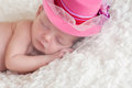 A portrait of a sleeping newborn baby girl wearing a fancy pink brimmed hat with netting over her face she is sleeping on white Royalty Free Stock Image