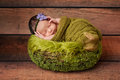 Portrait of a sleeping newborn girl day old baby in green basket she is swaddled in gauzy green material Stock Photo