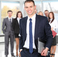 Portrait of a smart business man using laptop with colleagues in the background Royalty Free Stock Photo