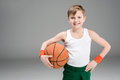 Portrait of smiling active boy in sportswear with basketball ball Royalty Free Stock Photo