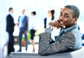 Portrait of smiling african american business man with executives working in background Royalty Free Stock Images