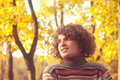 Portrait of smiling attractive man dressed in striped sweater, oudoor in autumn park. Royalty Free Stock Photo