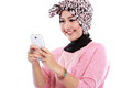 Portrait of a smiling beautiful muslim woman texting with her sm smartphone isolated over white background Royalty Free Stock Photo