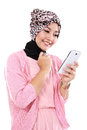 Portrait of a smiling beautiful muslim woman texting with her sm smartphone isolated over white background Royalty Free Stock Images