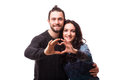 Portrait of smiling beauty girl and her handsome boyfriend making shape of heart by their hands.