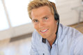 Portrait of smiling blond man talking on phone with headset attractive customer service representative Stock Photography