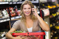 Portrait of smiling blonde woman buying vegetables and phoning at supermarket Royalty Free Stock Photography