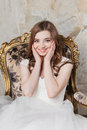Portrait of the smiling bride with perfect make up sitting on luxury chair Stock Image