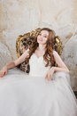 Portrait of the smiling bride with perfect make up sitting on retro luxury chair Stock Images