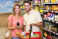 Portrait of smiling bright couple buying food products using shopping basket Royalty Free Stock Photo