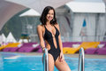 Portrait of smiling brunette girl in the black swimsuit with shapely body near the swimming pool on mountain resort Royalty Free Stock Photo