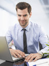 Portrait of a smiling businessman sitting in office with laptop Royalty Free Stock Photography