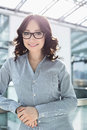 Portrait of smiling businesswoman leaning on railing in office Royalty Free Stock Photo