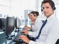 Portrait of smiling call center employee with colleagues behind Royalty Free Stock Images