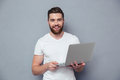 Portrait of a smiling casual man holding laptop Royalty Free Stock Photo