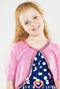 Portrait of smiling caucasian redhaired little girl standing aga against white vertical image composition Stock Photo