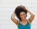 Portrait of a smiling cheerful woman close up posing with hand in hair outdoors Royalty Free Stock Images