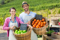 Portrait of smiling couple holding fresh fruits in wicker baskets Royalty Free Stock Photo