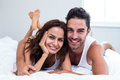 Portrait of smiling couple lying on bed Royalty Free Stock Photo