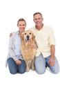 Portrait of smiling couple sitting together with their dog on white background Stock Images