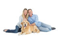 Portrait of smiling couple sitting together with their dog on white background Royalty Free Stock Images