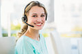 Portrait of a smiling creative businesswoman with earpiece in office Stock Photos