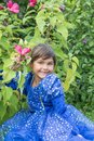 Portrait of smiling cute little girl at blooming hibiscus