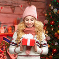 Portrait of a smiling cute woman opening gift box by christmas tree Royalty Free Stock Photo