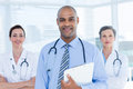 Portrait of smiling doctor holding file and standing in front of his colleagues the hospital Royalty Free Stock Image